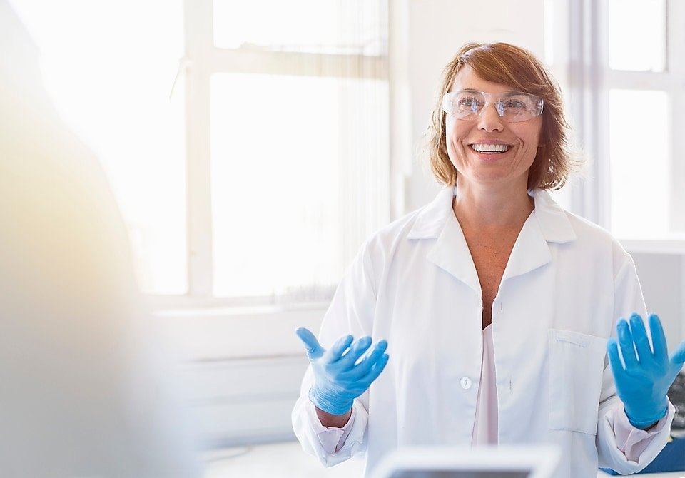 Woman in white lab coat wearing protective glasses