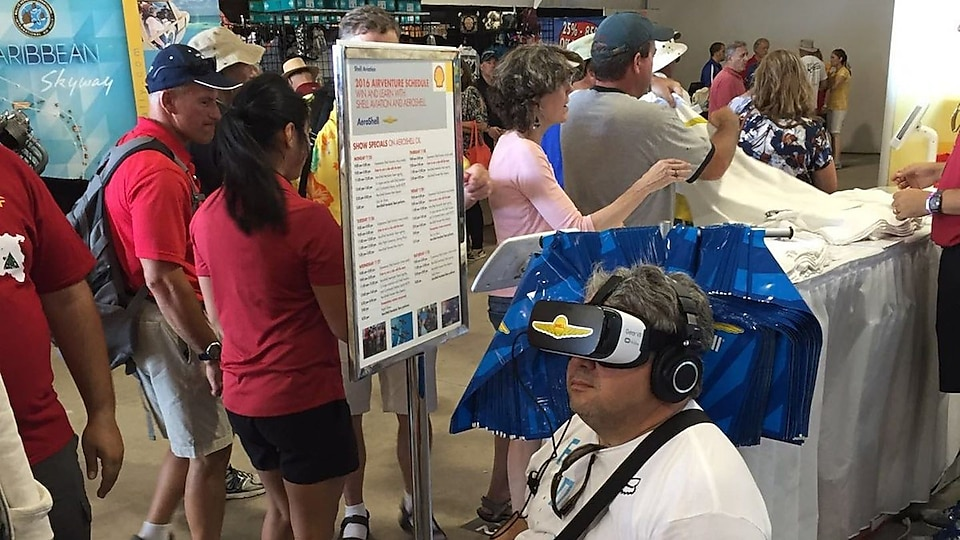 One Oshkosh attendee experiencing a virtual reality ride with the AeroShell Aerobatic Team at the AeroShell Booth