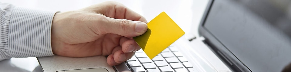 Male hands holding credit card when paying on your notebook