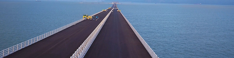 Construction workers lay the road surface on the Hong Kong-Zhuhai-Macau Bridge