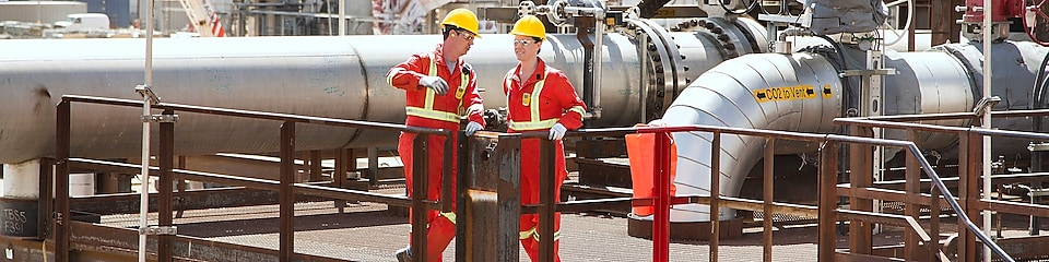 Two shell workers stand on stairs conducting catalyst inspection