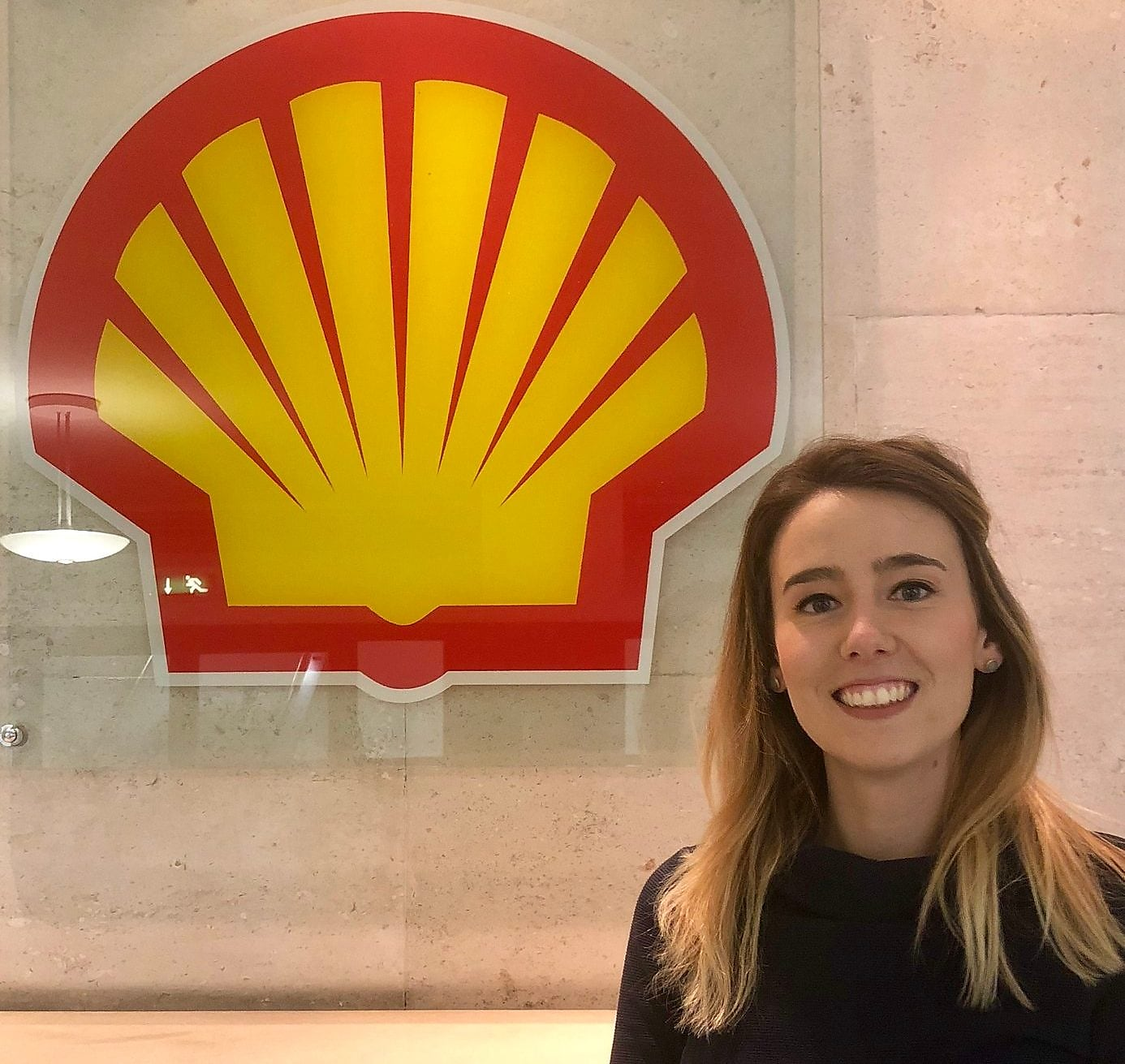 Emma is standing near The Shell Logo