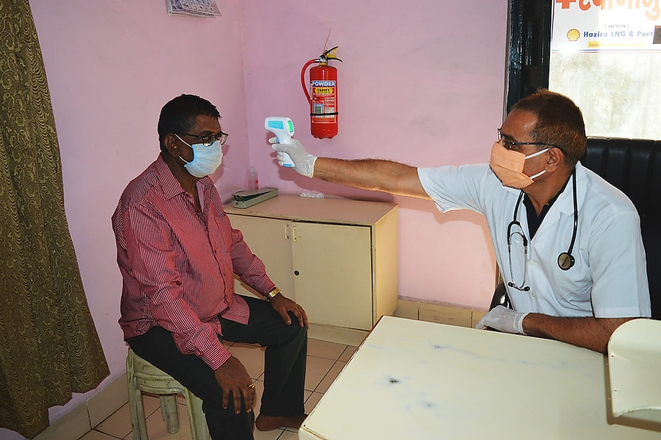 Dr Prakash Maradia takes the temperature of a patient