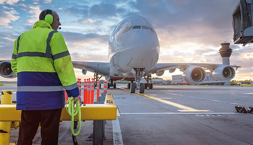 Airport worker standing by aeroplane