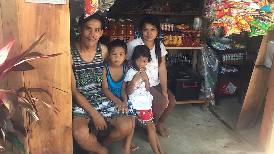 Marionito Bayonon sits with his family in the shop he's opened which has a freezer