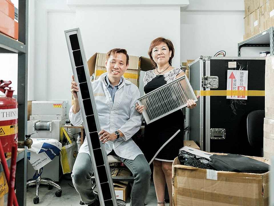 Terence Wong and his wife Julie holding their Solarite solar panels