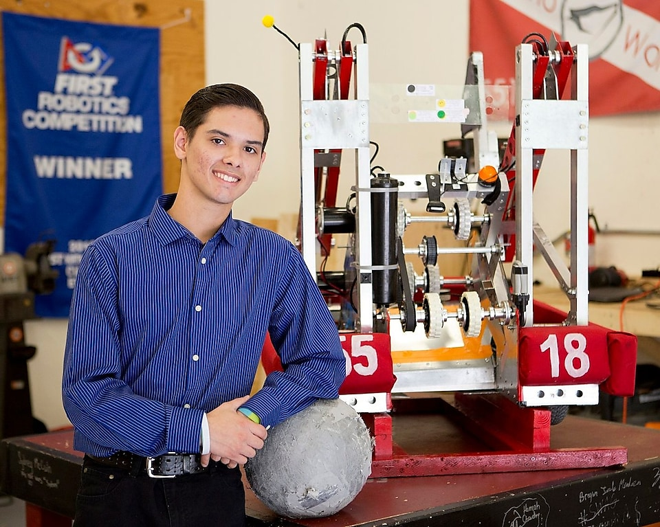 Miguel Castillo standing next to a robot he built.