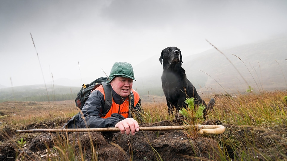 Man in Scottish Highlands with his dog