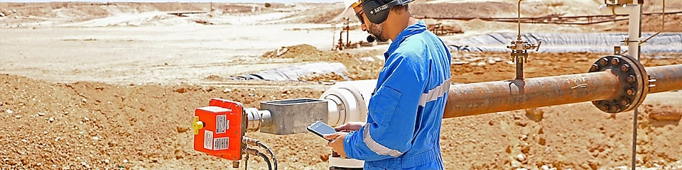 Technician Yahya Riyami checks his tablet to see if adjustments at a well head are showing up in real-time data