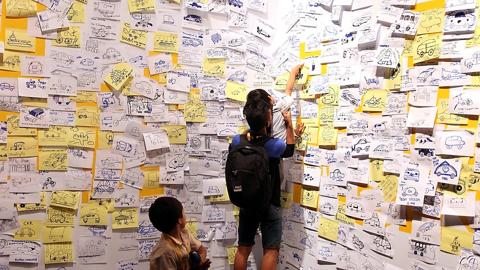 Visitors post 'ideas' on an interactive wall at the 'Experience' during day four of the Shell Eco-marathon