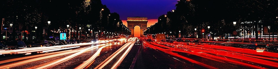 Image of the Arc de Triomphe and Champs-Élysées at night.