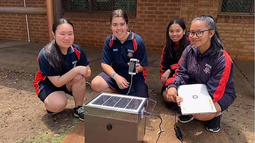 Picture of four students kneeling on the floor outside. One of them is holding a laptop and one of them is holding a phone, both of which are plugged into a solar powered charging device.