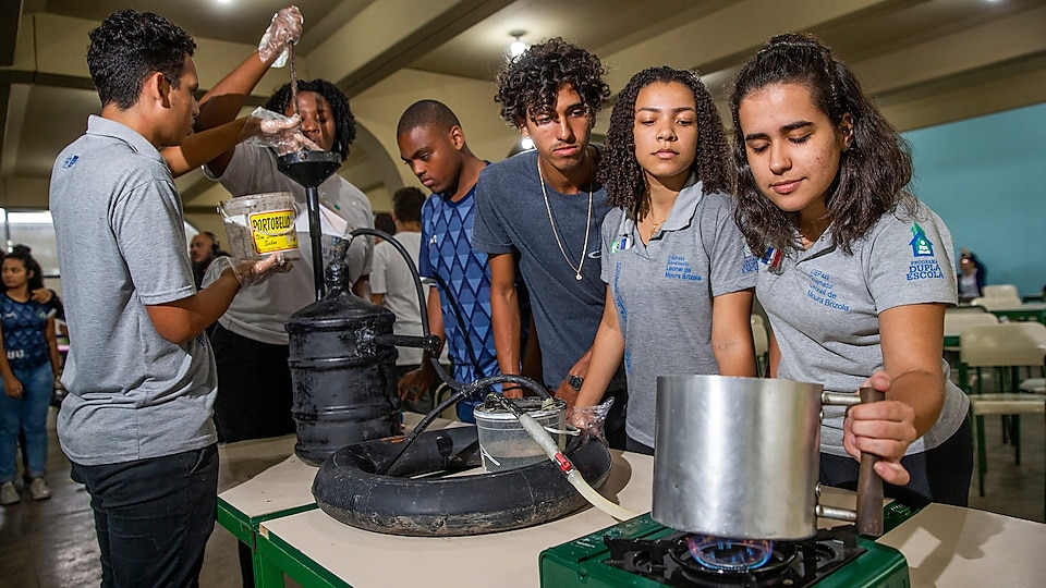 Picture of six students standing with a biodigester. Two of the students are pouring material into the biodigester via a funnel, while the other students are observing a pot being heated on a stove. The stove is being heated by the biodigester, which it is connected by a tube.