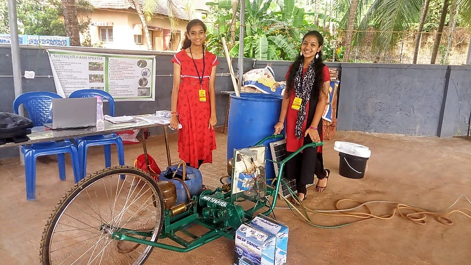 NXplorers student Neha Bhat standing beside her Agri-sprayer creation at an NXplorers event. Another NXplorers student is holding the handles of the Agri Sprayer and they are smiling at the camera.
