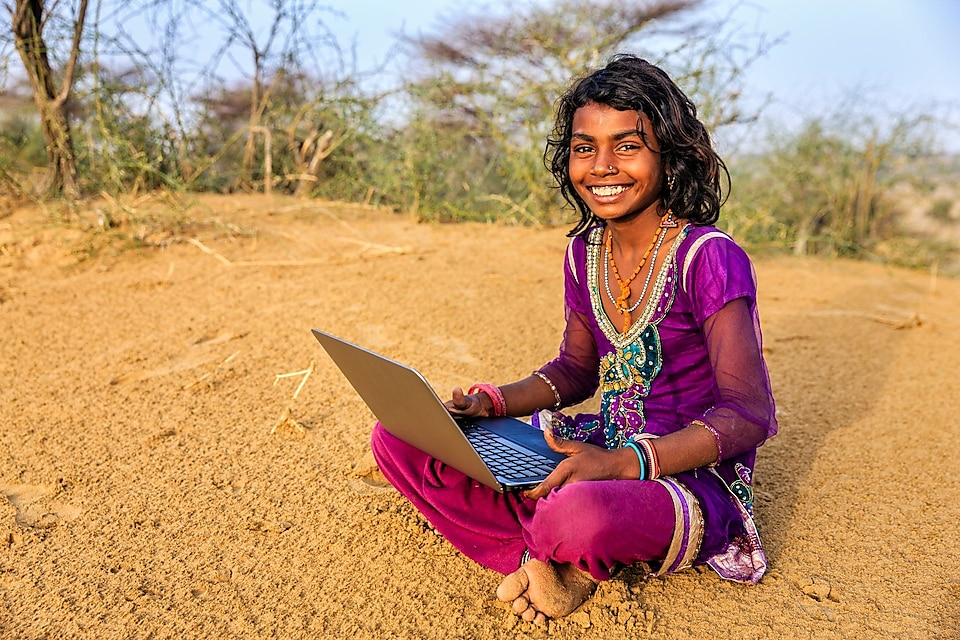 Young girl from India sitting on sand using a laptop