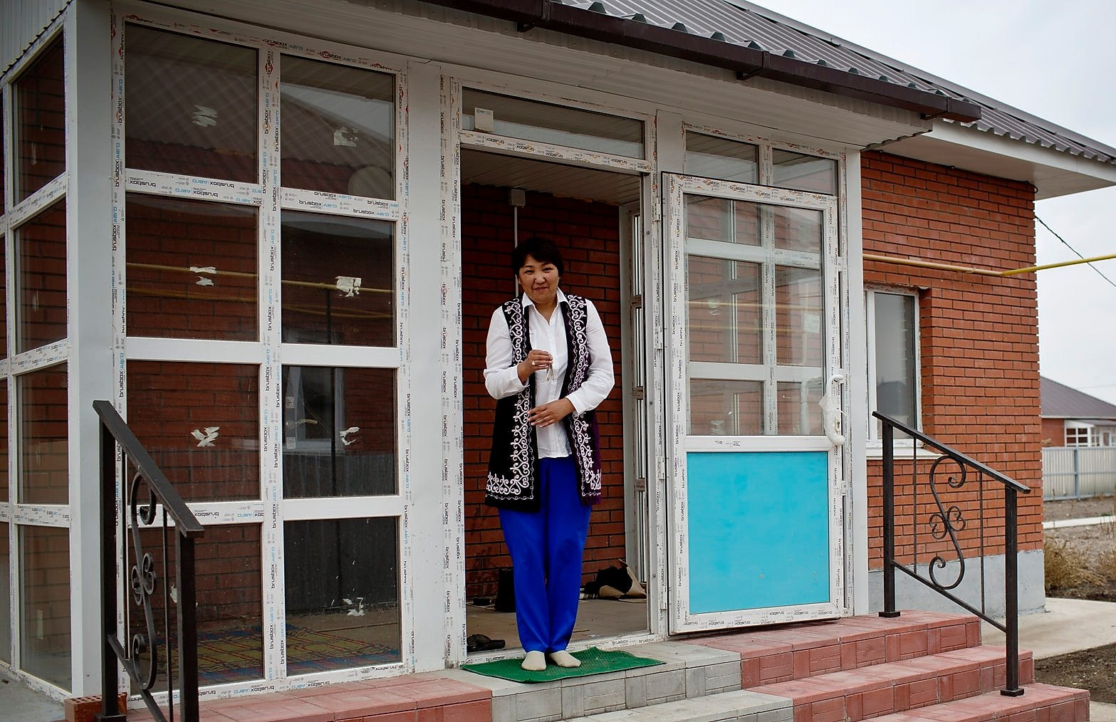 A lady standing outside her new house after relocating in Kazakhstan
